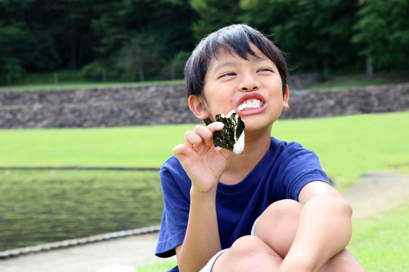 おにぎりを食べる少年